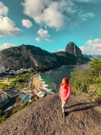 Mulher ruiva olhando para o lado esquerdo. Ela veste calça jeans, bota e uma blusa de manga comprida rosa, além de crachá de guia de turismo. Ao fundo uma praia, com o mar ao lado direito e a orla e cidade ao lado esquerdo.