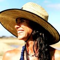 Close de mulher branca ruiva olhando para o lado direito, sorrindo e usando um chapéu de praia.