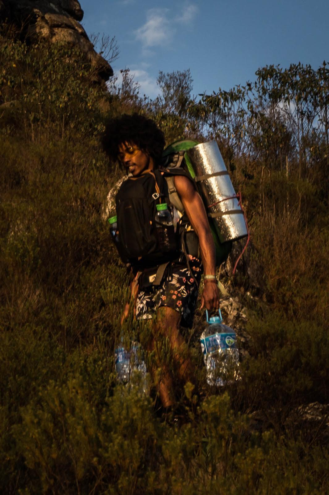 Foto de um homem negro, carregando uma mochila na frente do peito, uma mochila cargueira com um isolante térmico nas costas e um galão de água na mão esquerda. Ele está no meio de uma trilha com arbustos altos.