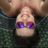 Close do rosto de mulher de óculos de sol de cabeça para baixo.