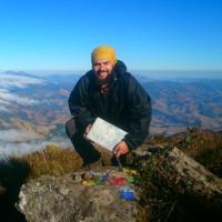 Homem branco de barba, sorrindo, veste casaco preto, calça preta, e um gorro amarelo. Segura uma folha na mão enquanto está agachado no pico de uma montanha, a Serra da Mantiqueira ao fundo.