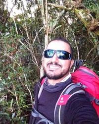 Selfie de homem branco com barba rala e cabelo curto, com um grande sorriso. Ele usa óculos de sol, veste camiseta preta e uma mochila vermelha. Ao fundo árvores de galhos finos.