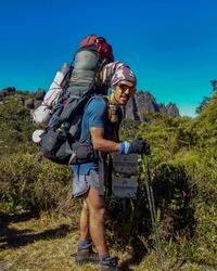 Foto de corpo todo do Vinicius. Ele carrega uma grande mochila cargueira, veste short e camiseta azul e se apoia em dois bastões de caminhada para equilibrar o peso. Ao fundo está uma montanha de rocha escura exposta e a vegetação da trilha do caminho.