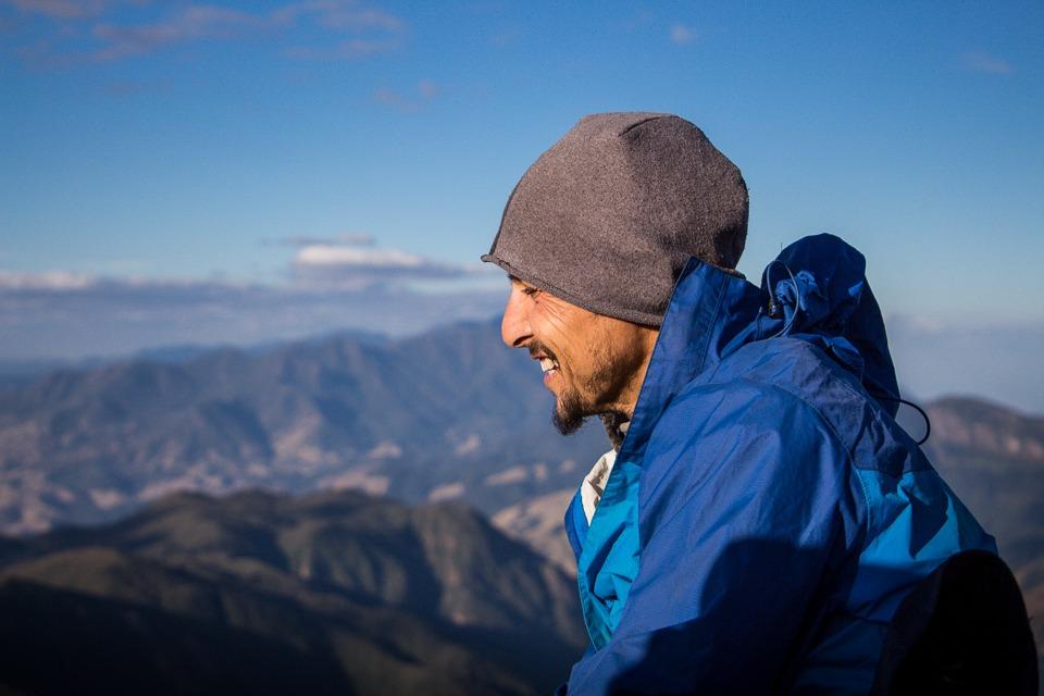 Foto de perfil do Will, ele sorri espontaneamente. Ele veste um gorro cinza e uma jaqueta azul cobalto.