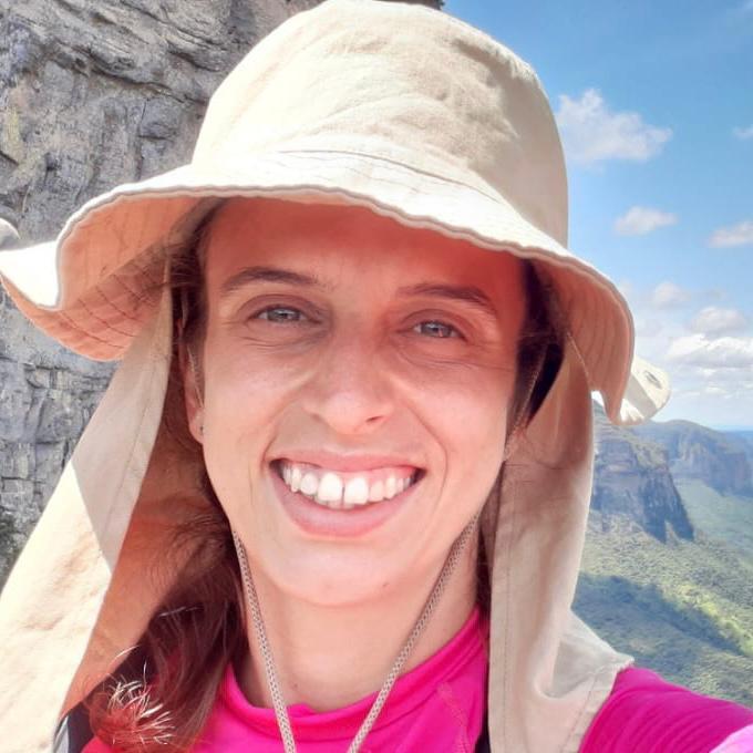 Close do rosto de mulher branca. Ela usa camiseta rosa e um chapeu areia, ao fundo as montanhas do vale do pati.