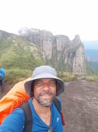 Selfie de um homem com barba sorrindo. Ele usa chapéu cinza, camiseta azul e uma mochila com capa de chuva laranja. Ao fundo um pouco de vegetação e um paredão de pedras.