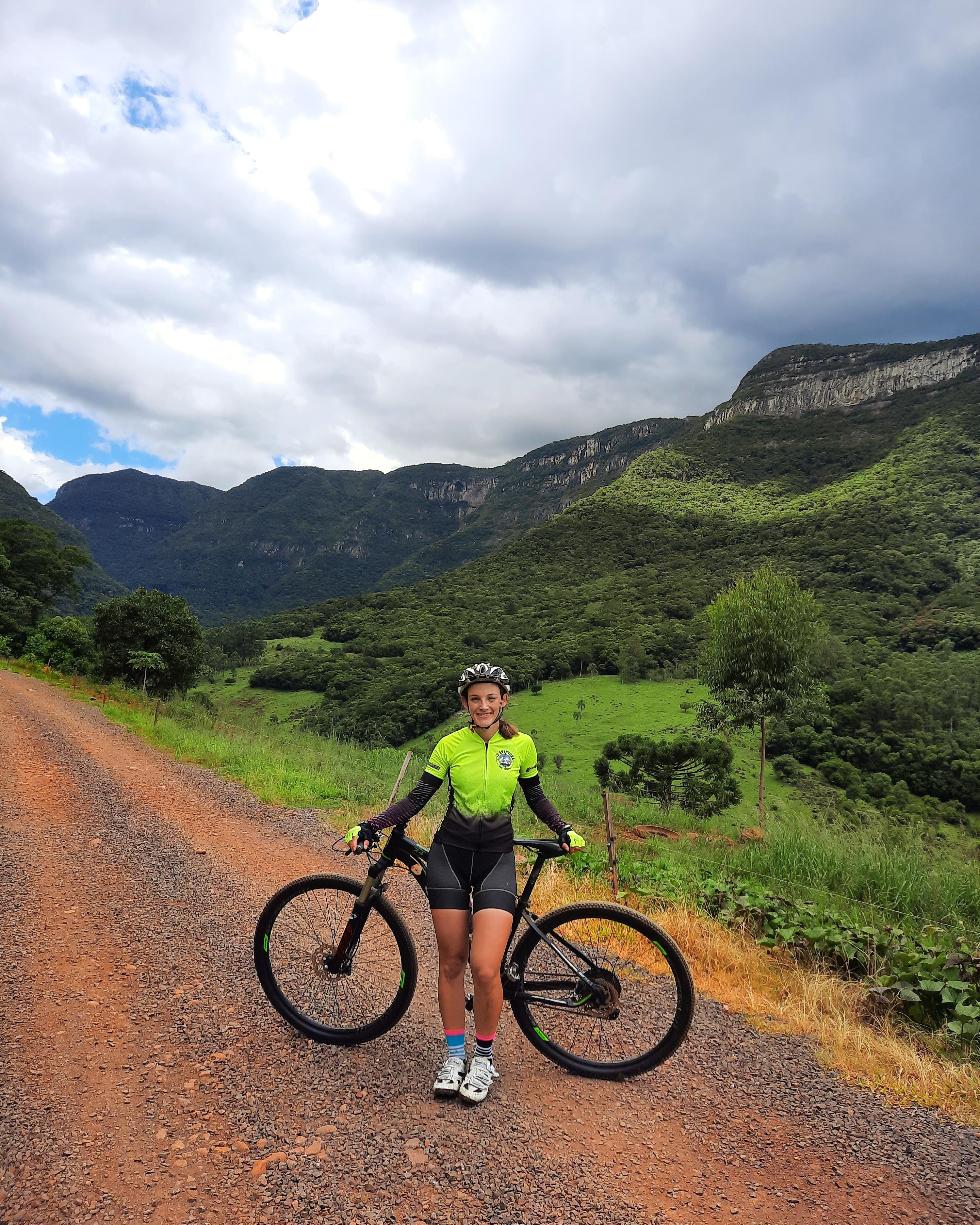 Foto de uma mulher branca em pé em frente a uma bicicleta. Ela veste um macacão de bike verde e preto, tênis, luva verde e capacete cinza. Ao fundo o início de uma montanha, com pequenos arbustos.