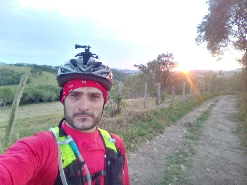 Sou um homem branco de olhos claros, com uma blusa vermelha e com uma bandana vermelha com um capacete de andar de bicicleta.