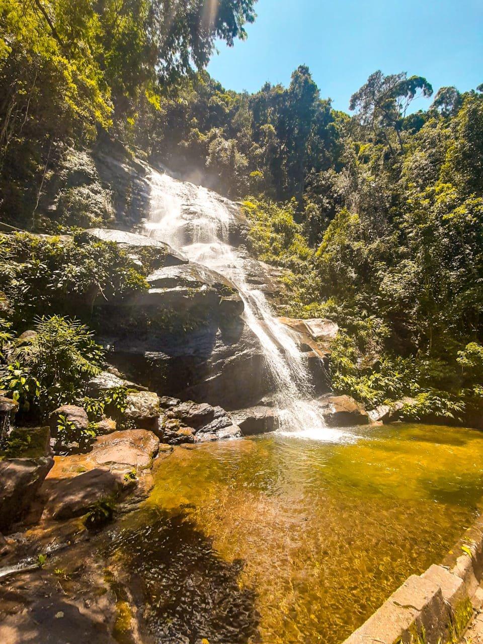 Cascatinha Taunay. A cachoeira possui águas cristalinas de coloração alaranjada e muitas pedras. No centro está a queda d'água com fluxo de água mediano e com muita vegetação ao seu redor. Esta vegetação possui coloração verde escuro, muitas plantas, folhas e cipós.
