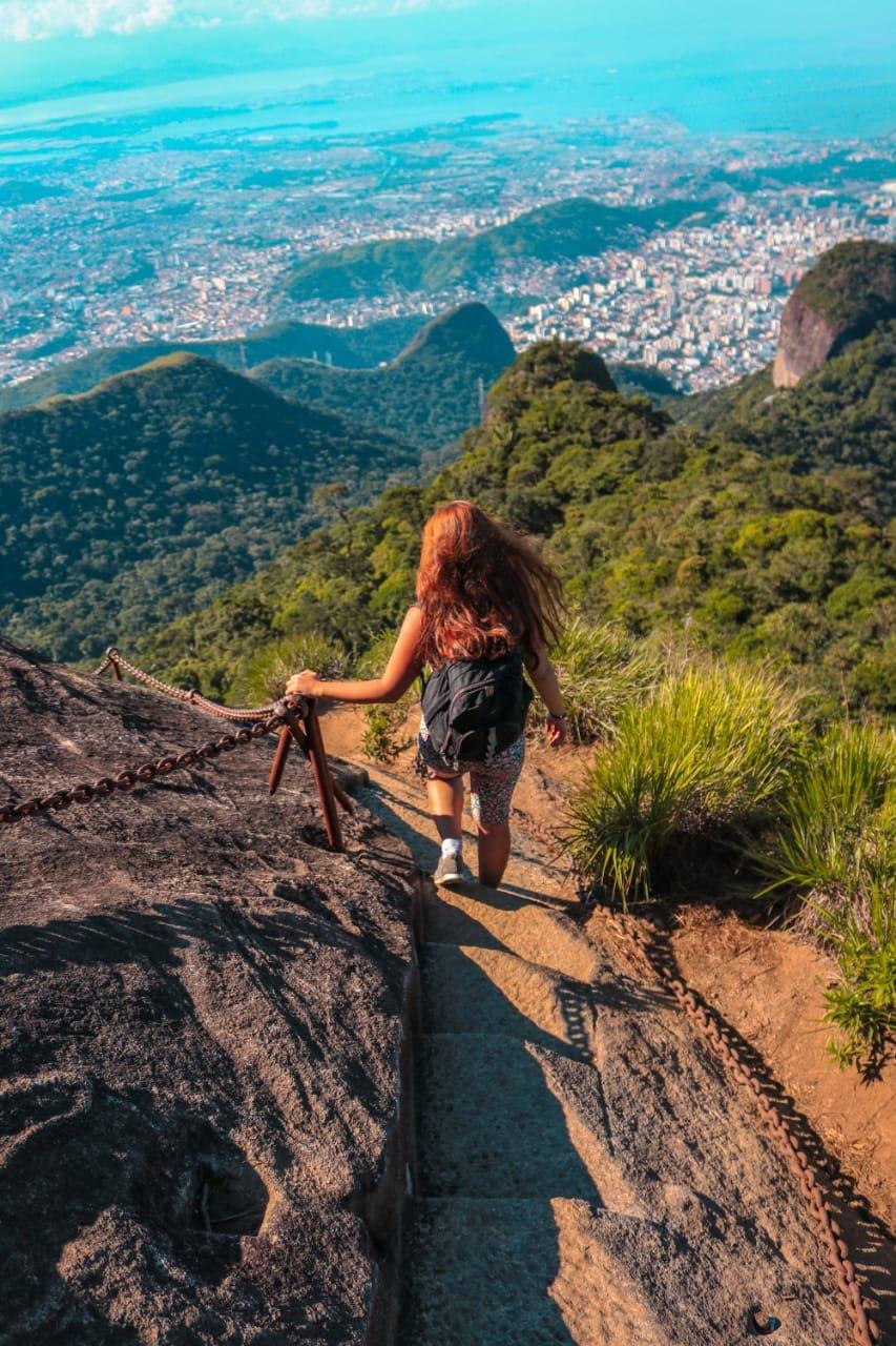 Uma mulher está descendo a escadaria do Pico da Tijuca, a foto foi tirada de cima do pico de modo que apenas é possível visualizar as costas dessa mulher. Na esquerda inferior da imagem está uma rocha de tonalidade escura que fica às margens da escadaria da trilha, não é possível ver seu começo ou fim. Na parte superior bem ao fundo está a cidade do Rio de Janeiro. Uma densa mata com características de vegetação de mata atlântica e tonalidades verdes preenche as outras áreas da imagem. A viajante possui cabelo liso ruivo e eles estão soltos, veste uma bermuda com estampas de flores pequenas e coloridas, uma mochila preta e um tênis cinza.