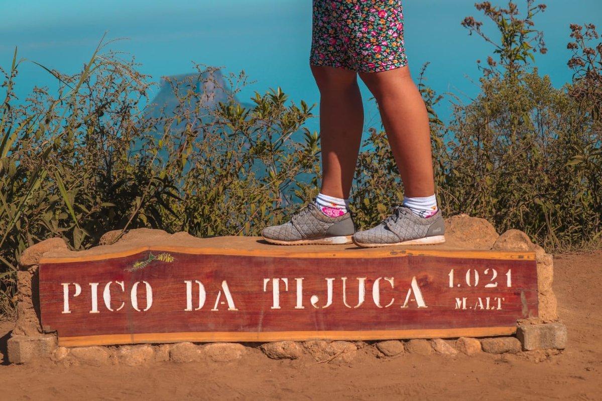 """Uma viajante está em cima de uma placa de madeira que está sobre o chão. Na placa está escrito com tinta branca """"Pico da Tijuca"""". Atrás da placa estão algumas plantas com caules e folhas finas. Ao fundo das folhas, é possível identificar o pão de açúcar. A viajante veste tênis cinza, meias brancas e bermuda com estampa florida."""