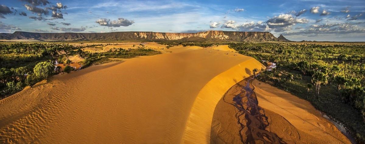Paisagem de uma grande duna de areia em tom amarelo-alaranjado. Na lateral direita a duna desce alguns metros até um leito de um rio quase seco. Ao fundo, um campo quase deserto, com vegetação em apenas algumas partes, segue até uma cadeia de montanhas de coloração amarela que está ininterrupta na imagem. Acima, um céu azul com poucas nuvens.